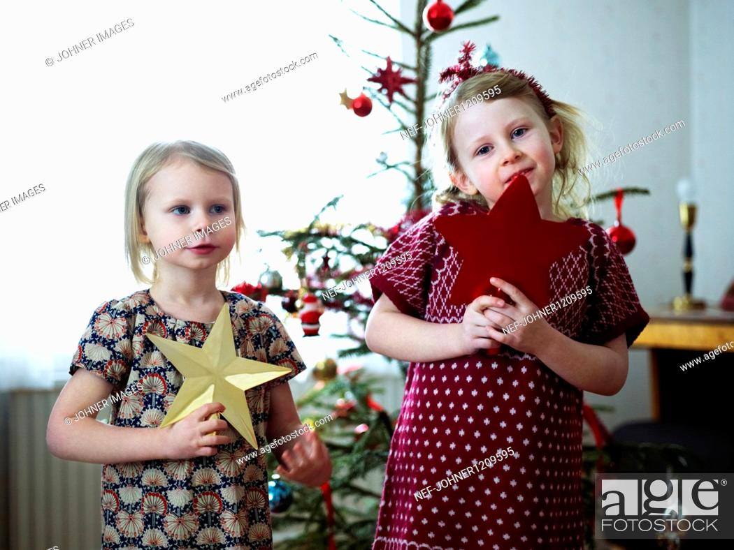 Stock Photo: Two girls decorating christmas tree.