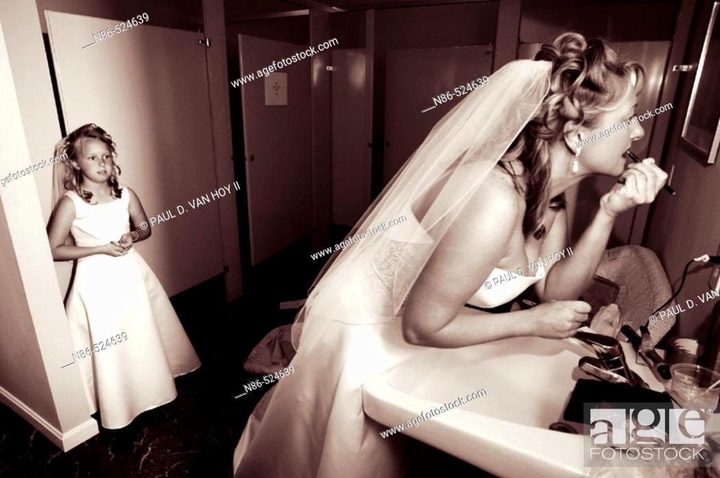 Stock Photo: Bride preparing in bathroom with flower girl.