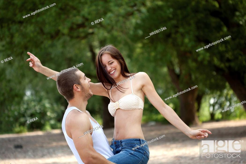 Stock Photo: Young man carrying woman outdoors.