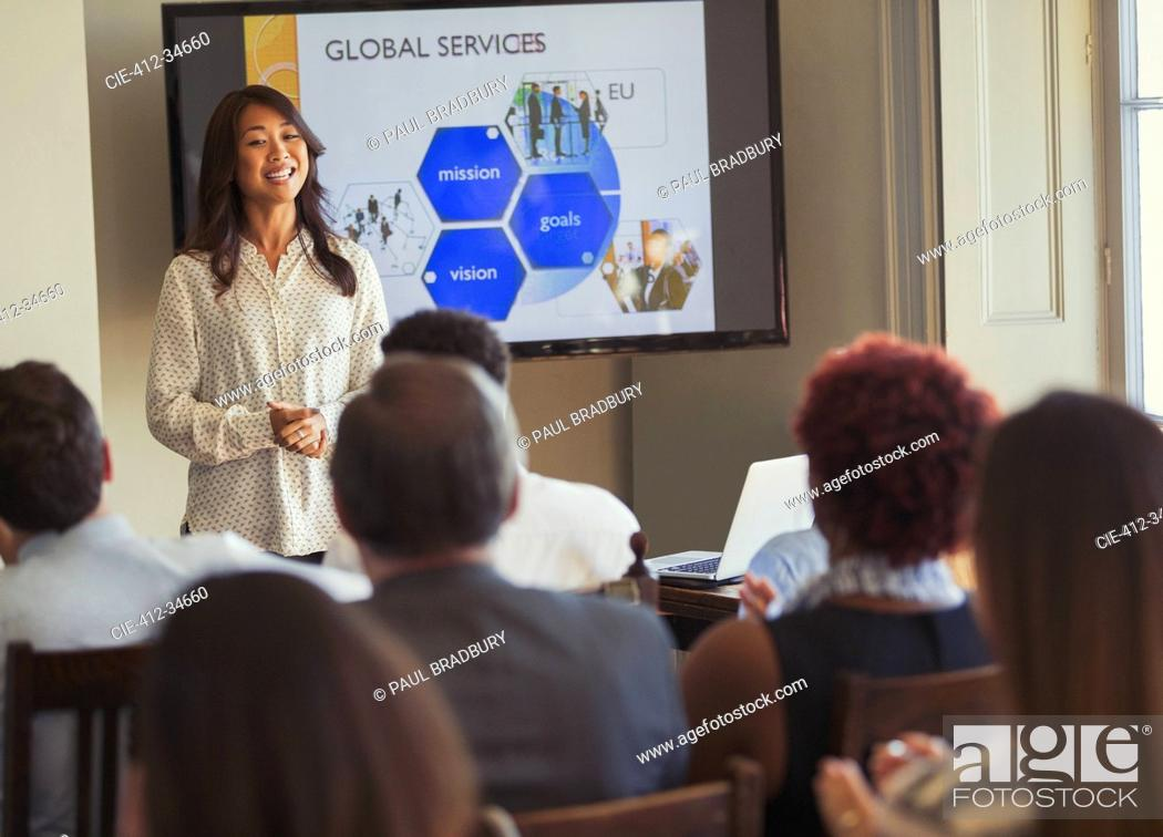 Stock Photo: Smiling businesswoman leading business conference presentation at television screen.