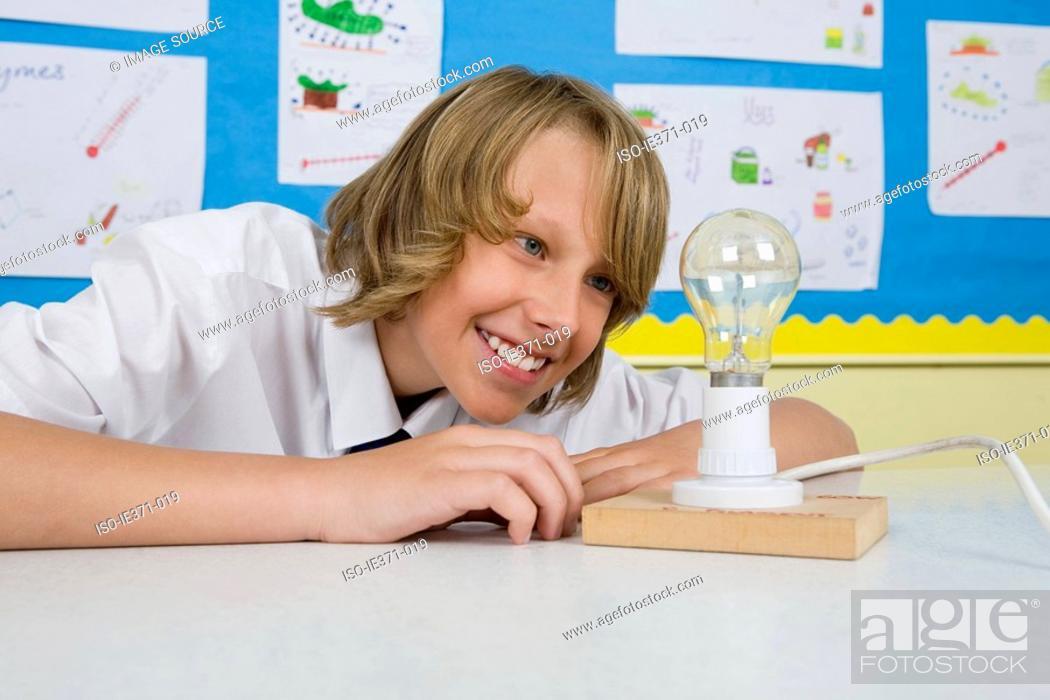 Stock Photo: Boy looking at lightbulb.