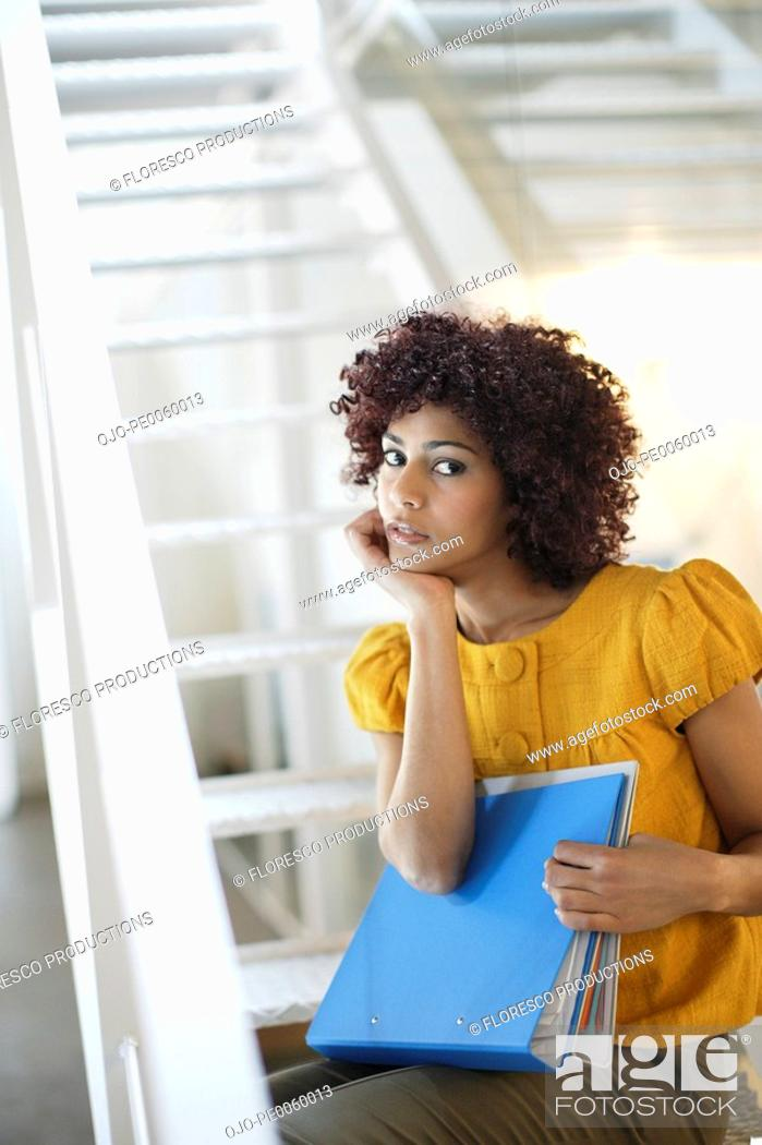 Stock Photo: Businesswoman in office space holding binders at bottom of staircase.