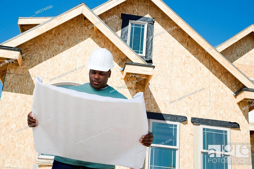 Stock Photo: A builder holding a blueprint.
