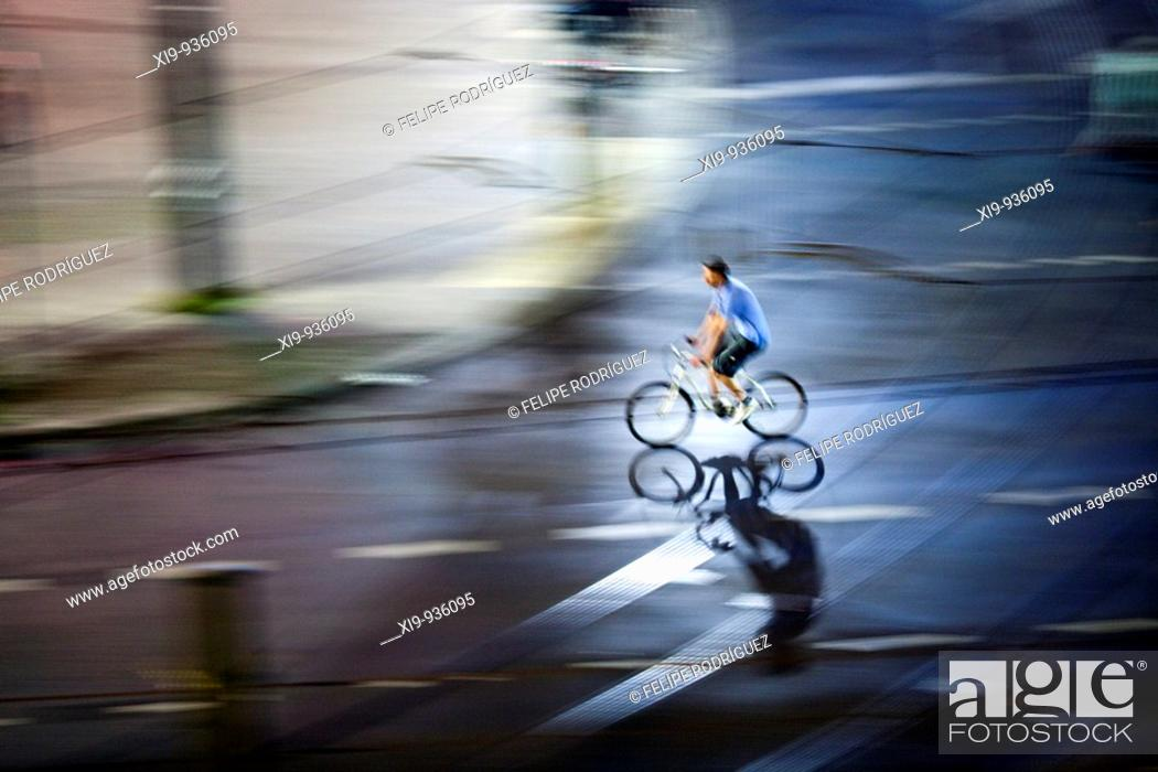 Stock Photo: Panning shot of a cyclist by night, Berlin, Germany.