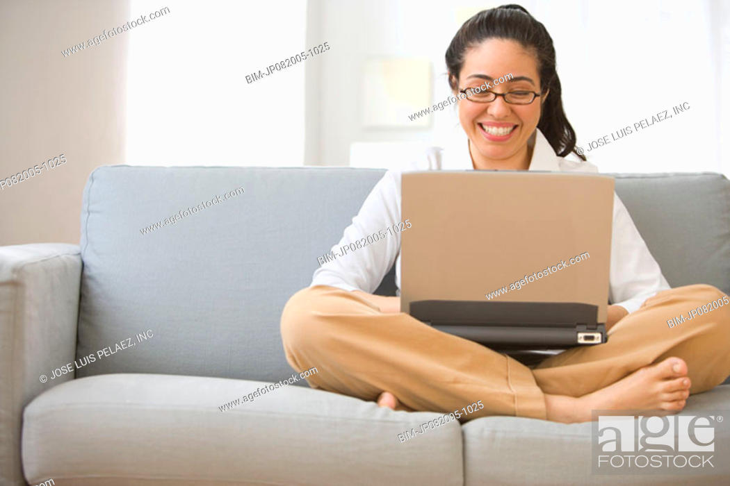 Stock Photo: Woman sitting on couch with lap top.