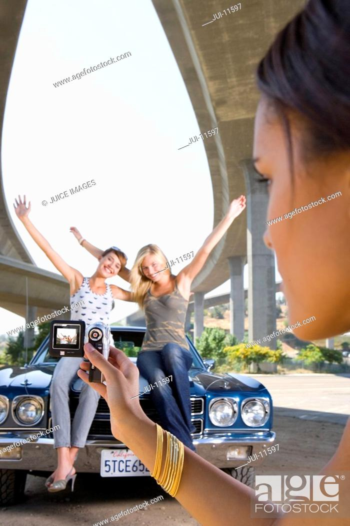 Stock Photo: Young woman taking photograph of friends on bonnet of car beneath overpass, close-up.