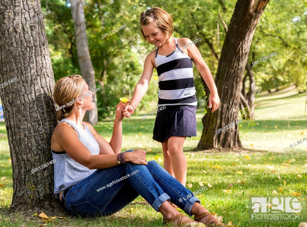 Photo de stock: Mother getting a flower from her daughter while spending quality time at a park during a family outing; Edmonton, Alberta, Canada.