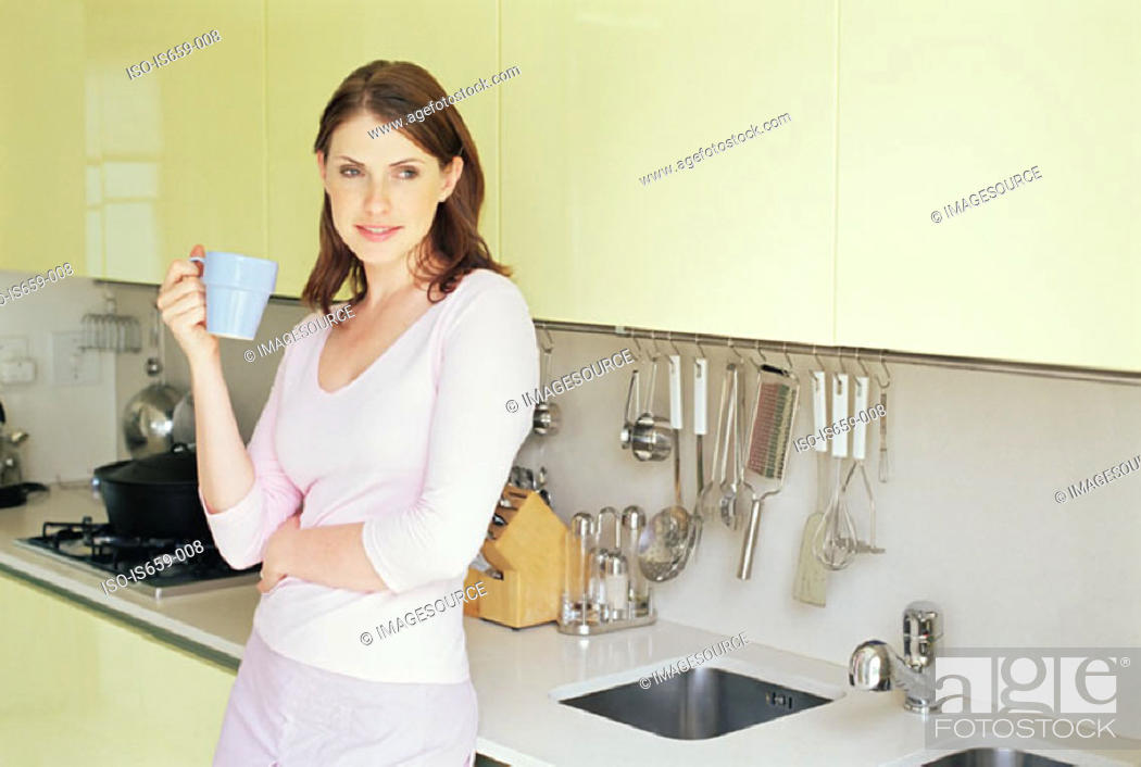 Stock Photo: Woman having a drink in the kitchen.