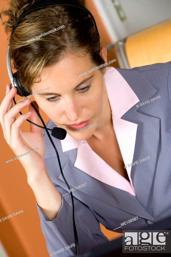 Stock Photo: Woman in early 20s working on computer and talking on headset telephone at home.