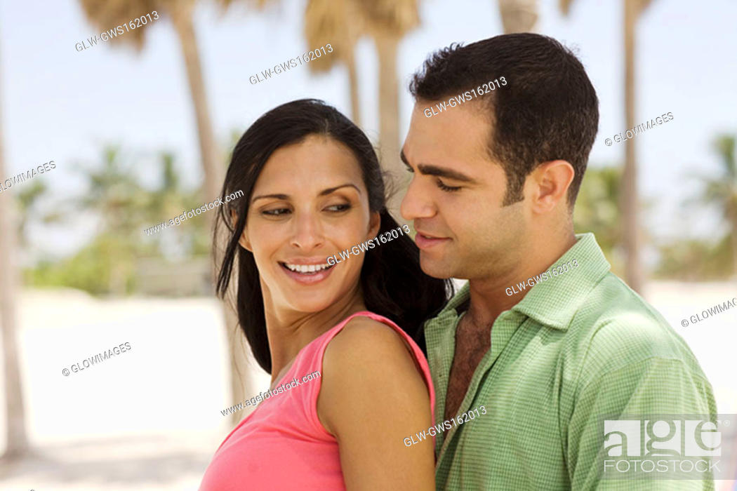 Stock Photo: Side profile of a young couple smiling.