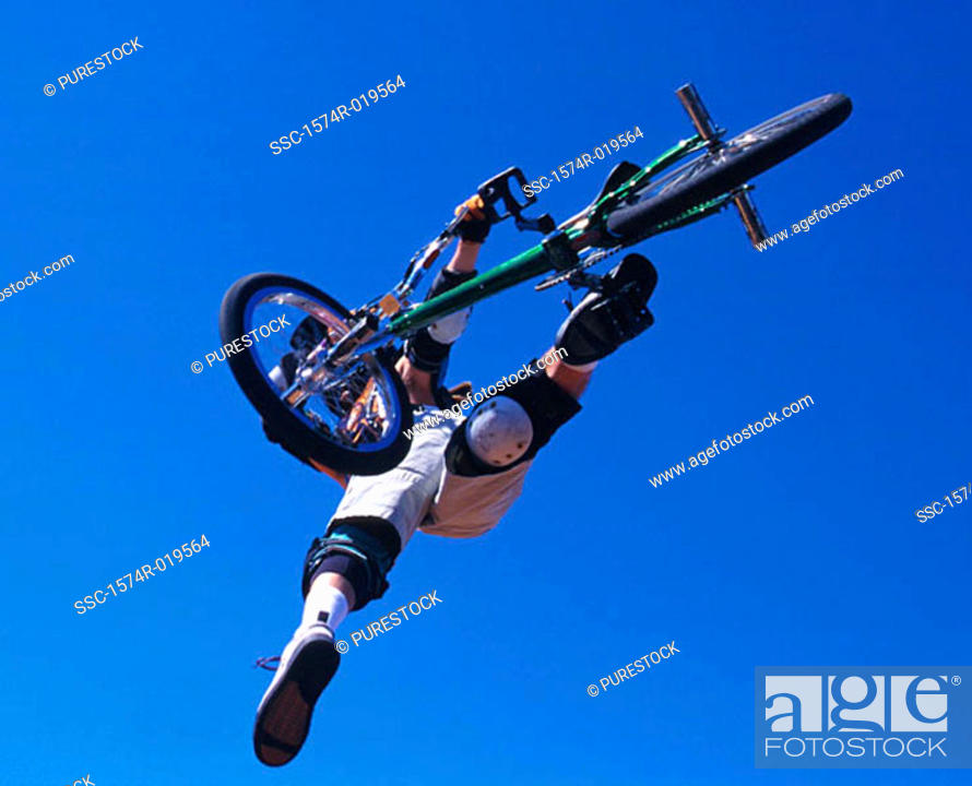 Stock Photo: Low angle view of a person performing stunts on a bicycle.