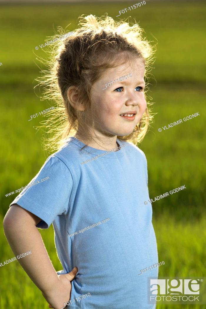 Stock Photo: A young girl standing in a field and looking away.