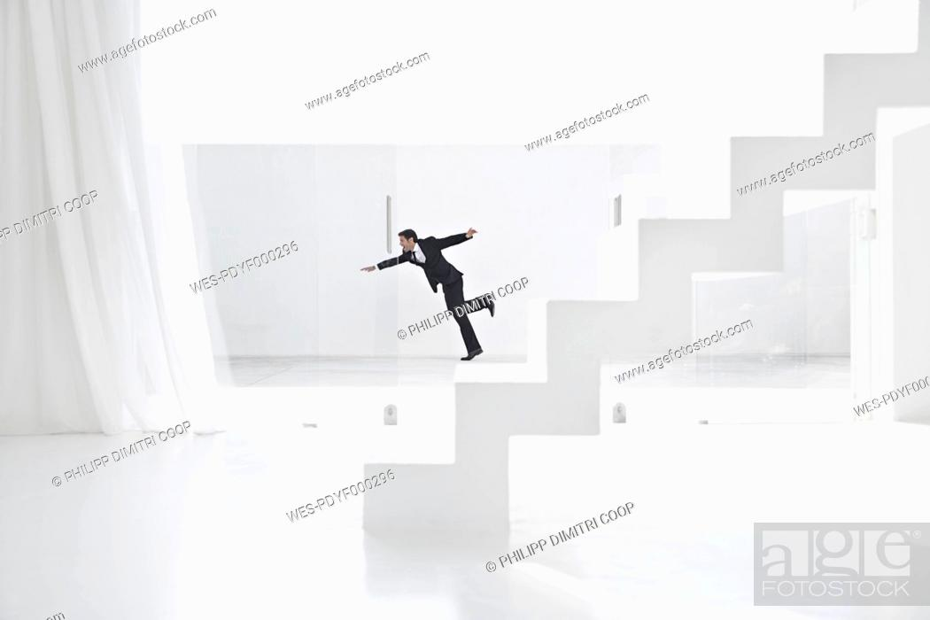 Stock Photo: Spain, Businessman falling down from ladders.