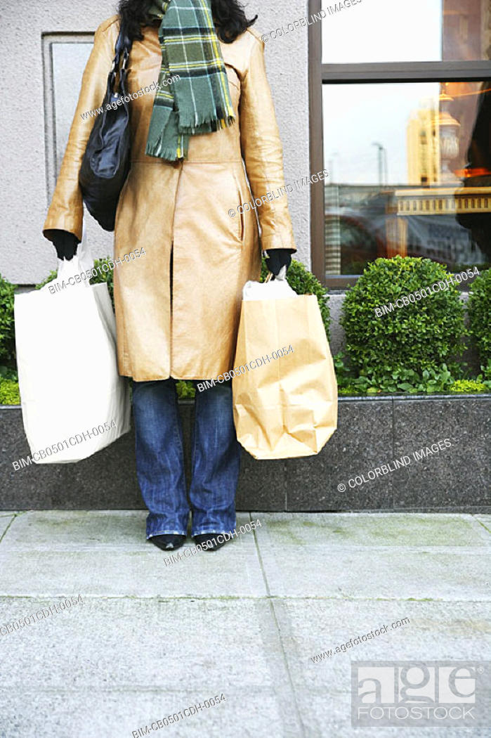 Stock Photo: Low section of woman with shopping bags.