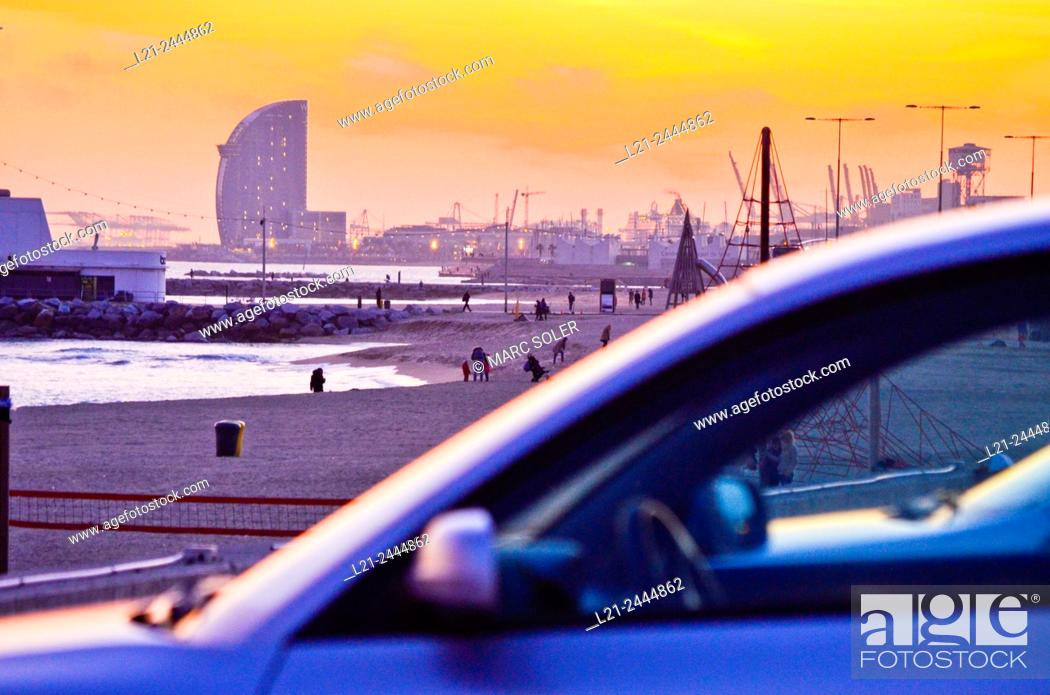 Stock Photo: Beach at sunset. First, detail of a blurred car. In the background, beach and Hotel W by Ricardo Bofill architect. Hotel W, aka Vela Hotel.