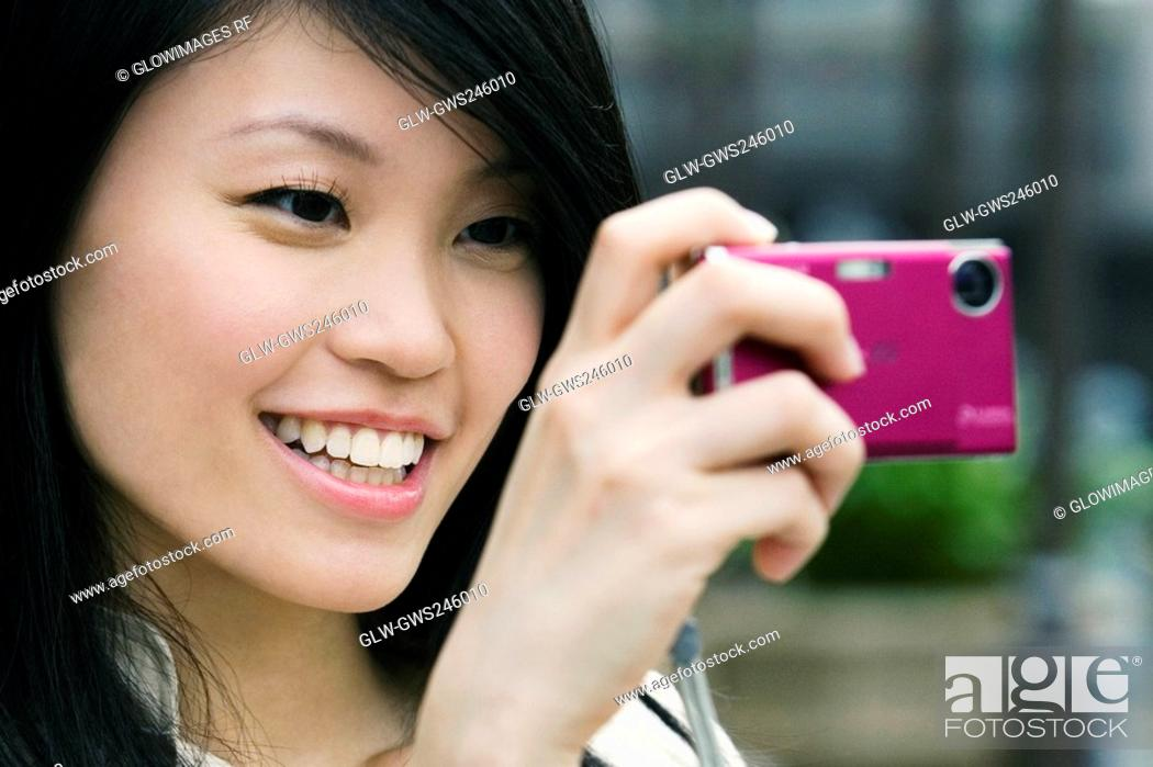 Stock Photo: Close-up of a young woman taking a picture with a digital camera.