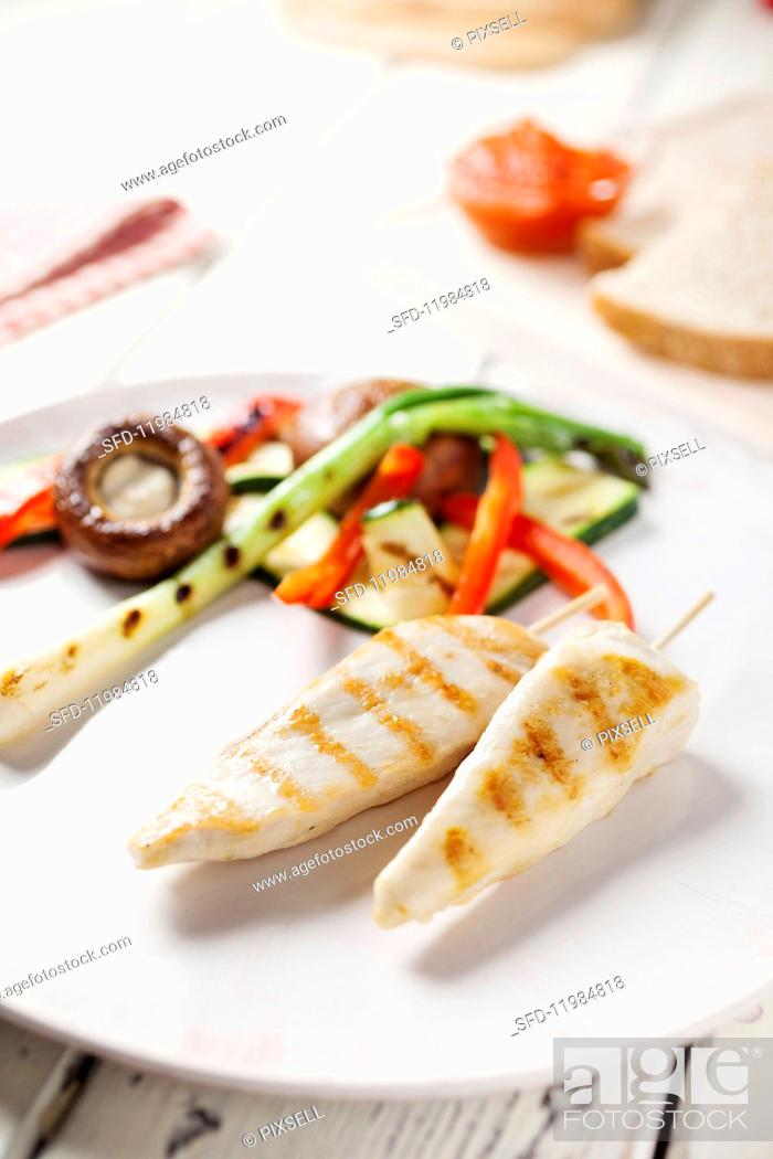 Stock Photo: Marinated grilled chicken strips with vegetables.