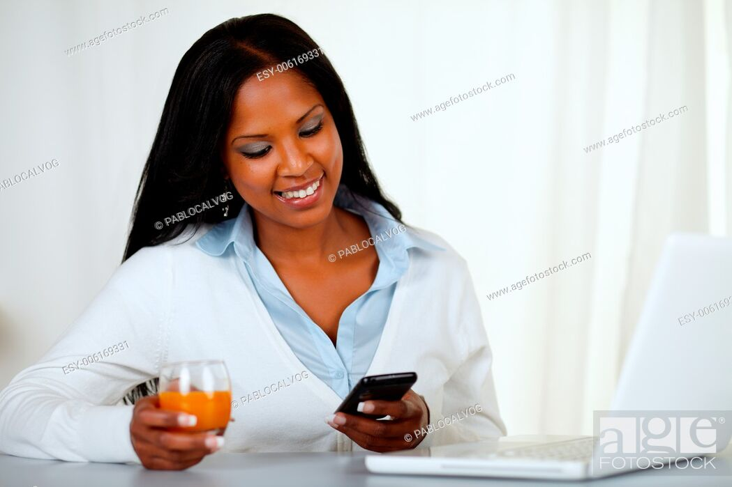 Stock Photo: Portrait of a young woman sending a message by the mobile at home indoor.