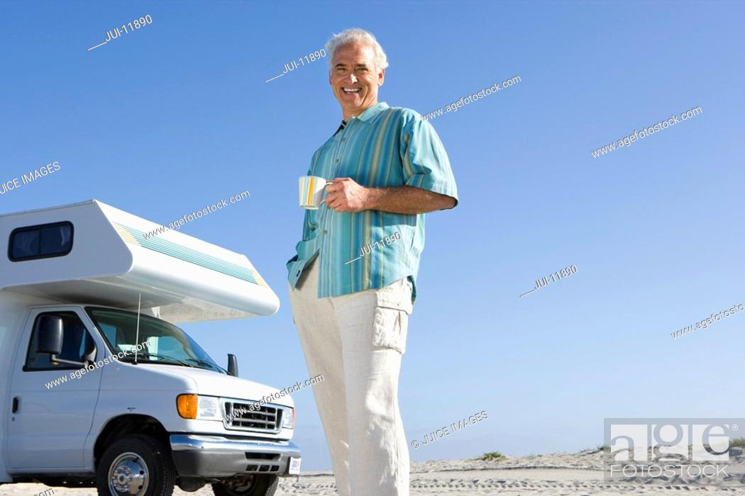 Stock Photo: Mature man with mug by motor home on beach, smiling, portrait, low angle view.