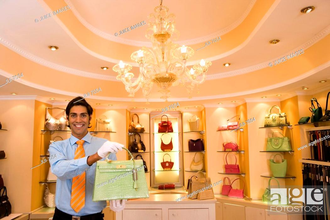 Stock Photo: Male shop assistant, in white gloves, standing in front of shelf display in glamorous boutique, holding green designer handbag, front view, portrait.