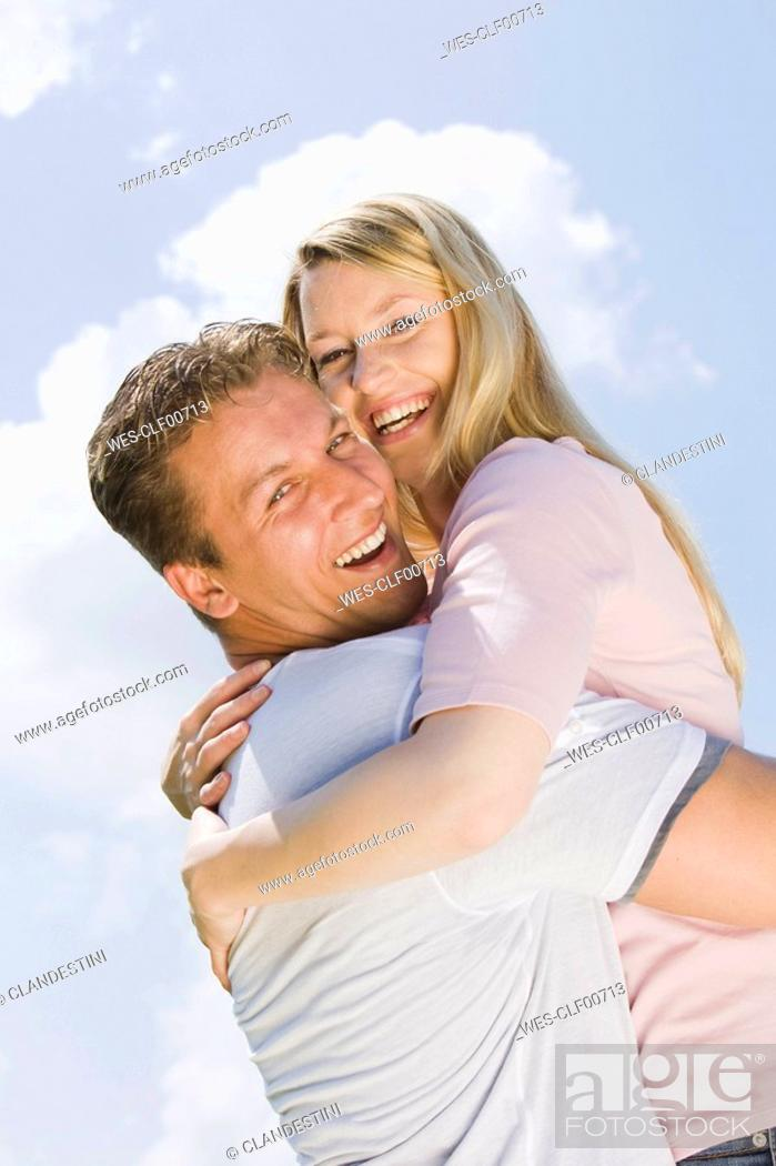Stock Photo: Germany, Bavaria, Munich, Young couple, man lifting woman, side view, portrait.