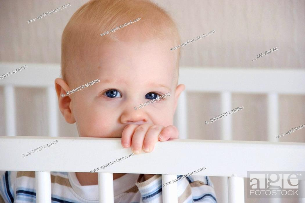 Stock Photo: A young fair-haired, blue-eyed baby boy stands in his white crib, looking at the camera.