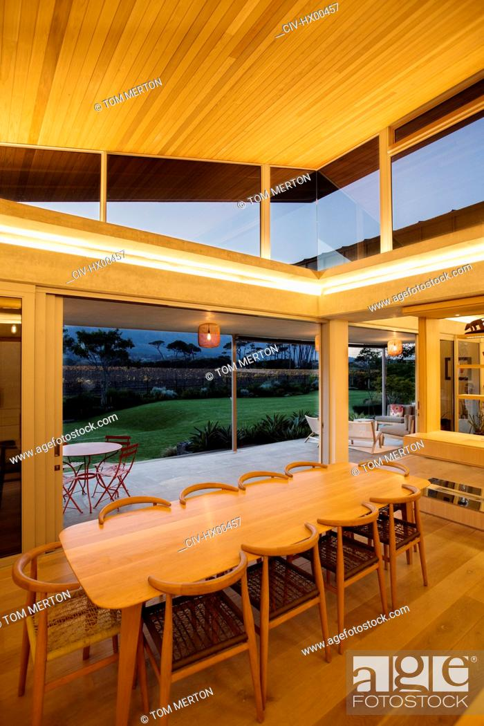 Photo de stock: Illuminated slanted wood ceiling over long dining table.