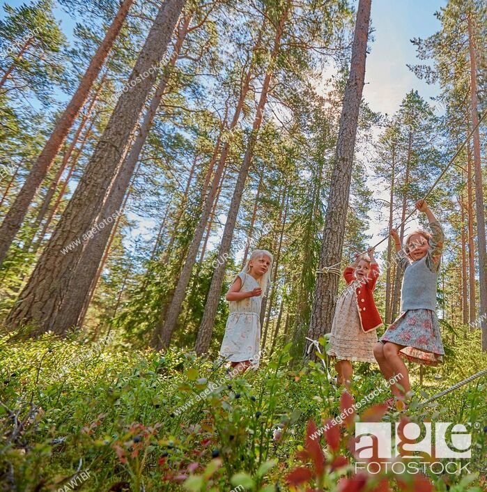 Imagen: Three girls dressed in retro clothing balancing on forest ropes.