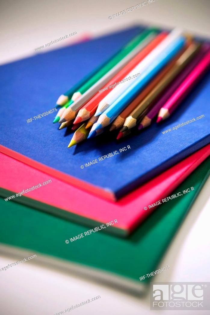 Stock Photo: colored pencils on the pile of notes.