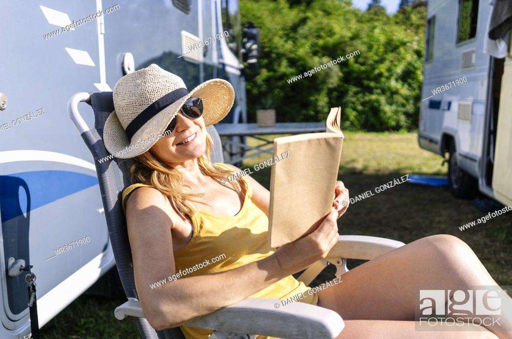 Stock Photo: Relaxed woman sitting next to camper enjoying vacation and reading a book.