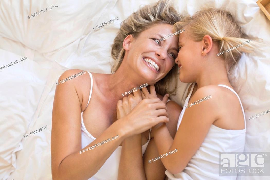 Stock Photo: Happy mother and daughter laying face to face in bed.
