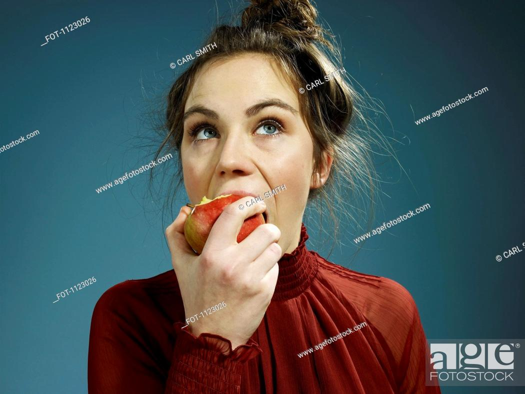 Stock Photo: A young hip woman eating an apple.