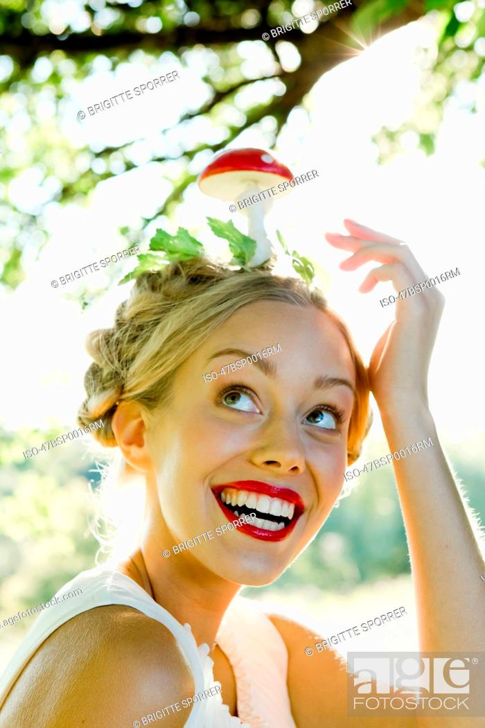 Stock Photo: Woman balancing mushroom on her head.
