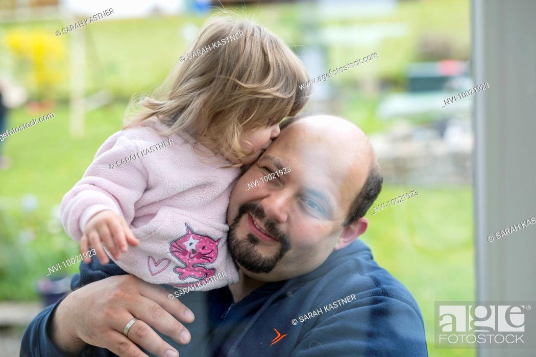 Stock Photo: Little girl kissing her father.