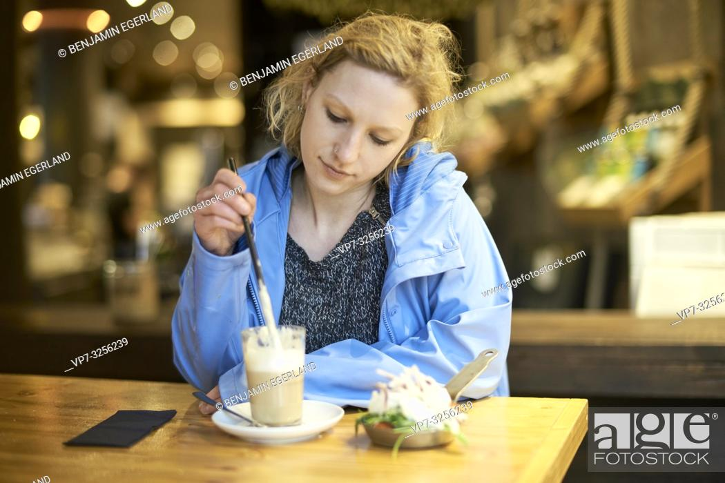Stock Photo: Young thoughtful woman stirring latte macchiato with drinking straw, in cafe, taking a break alone, thinking, in Munich, Germany.