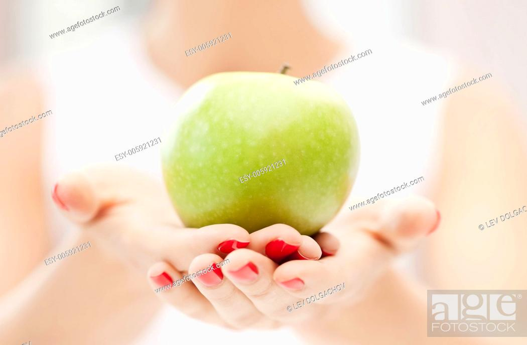 Imagen: bright picture of female hands with green apple.
