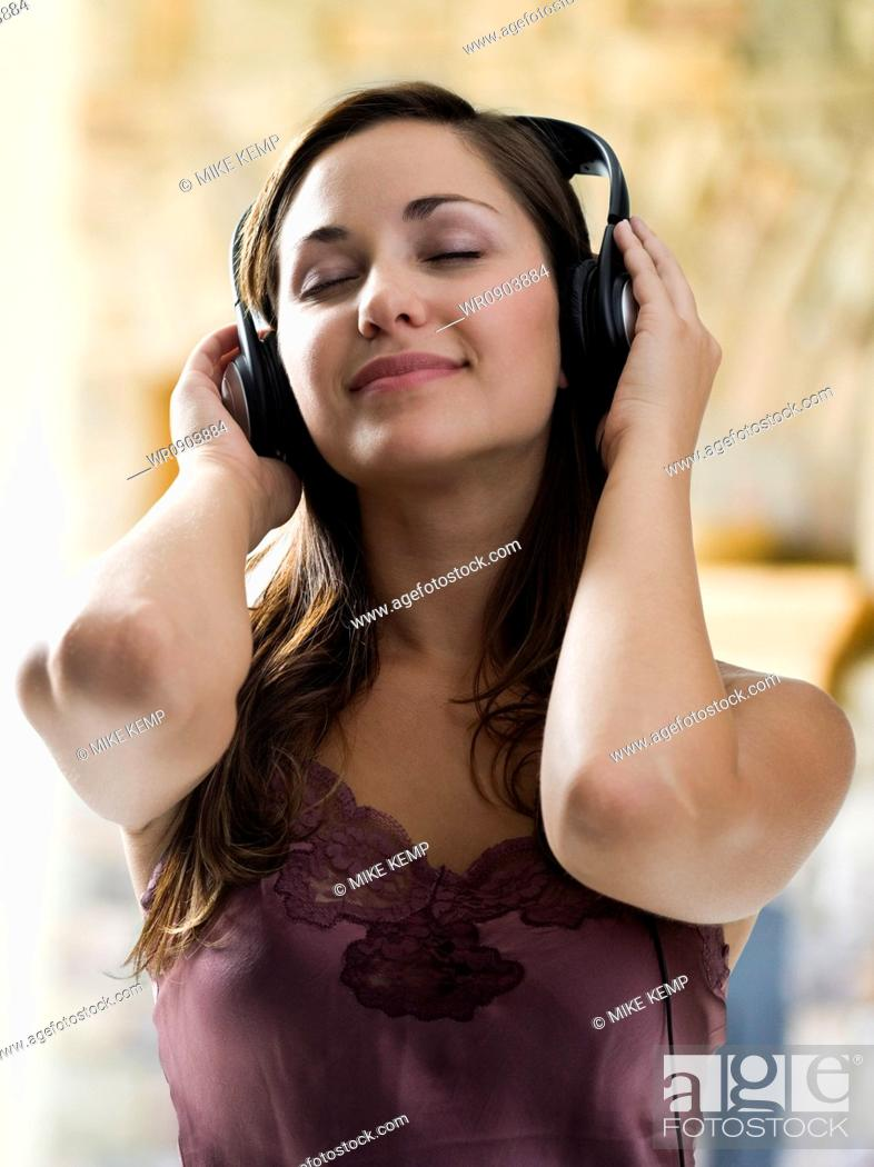 Imagen: Young woman listening to music on headphones.