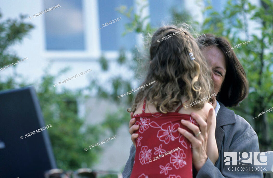Stock Photo: A woman, businesswoman, mother, 40-45 45-50 years old, and a little girl, young, 1-5 5-10 years old, in the summerly garden.