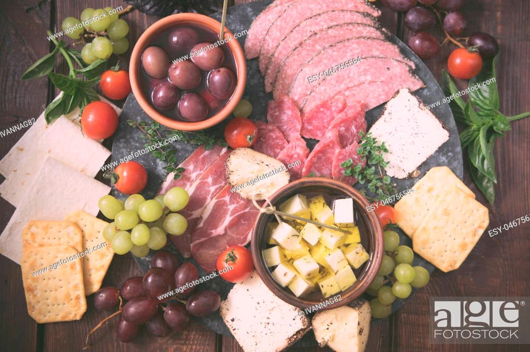 Stock Photo: Cheese and meat appetizer selection. Variety of cheese, salami, prosciutto, bread, baguette, grapes, olives.