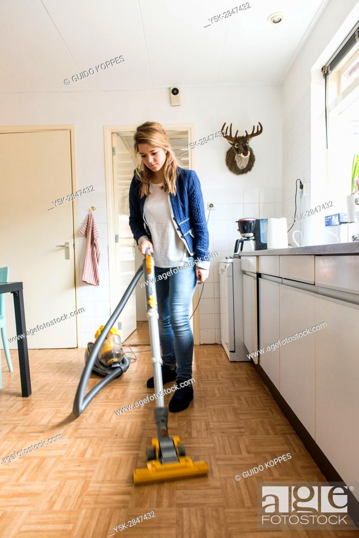 Photo de stock: Tilburg, Netherlands. Young caucasian woman dustcleaning the floor of her kitchen.