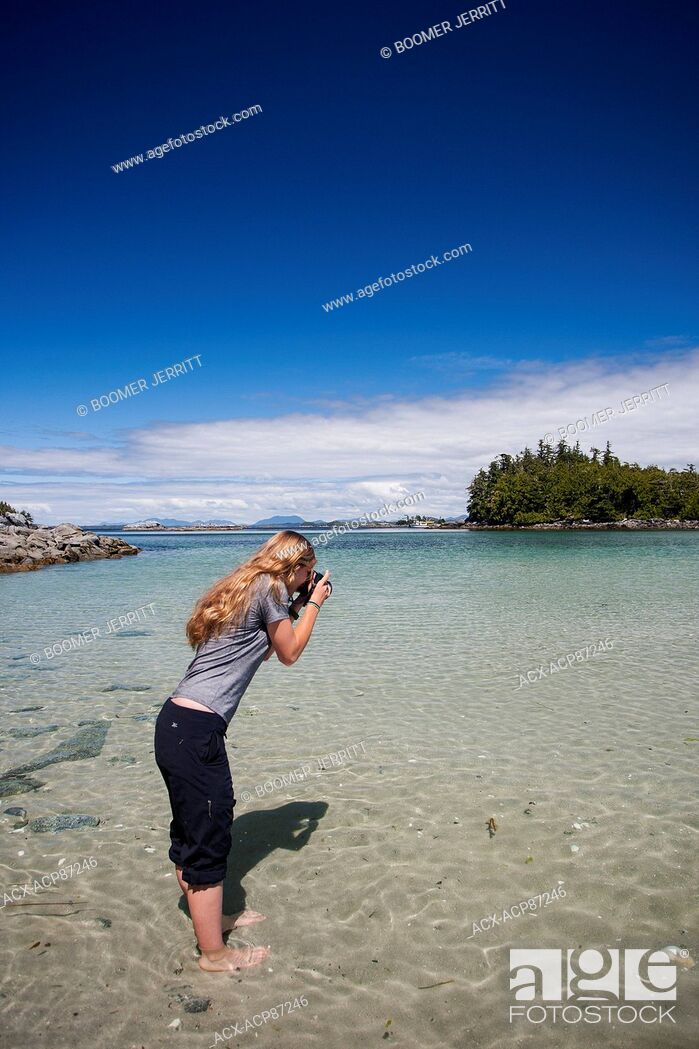 Stock Photo: A young female photographer photographs a west coast scenic while exploring at the Mcmullin group of Islets. The great bear rain forest, Fiordland.