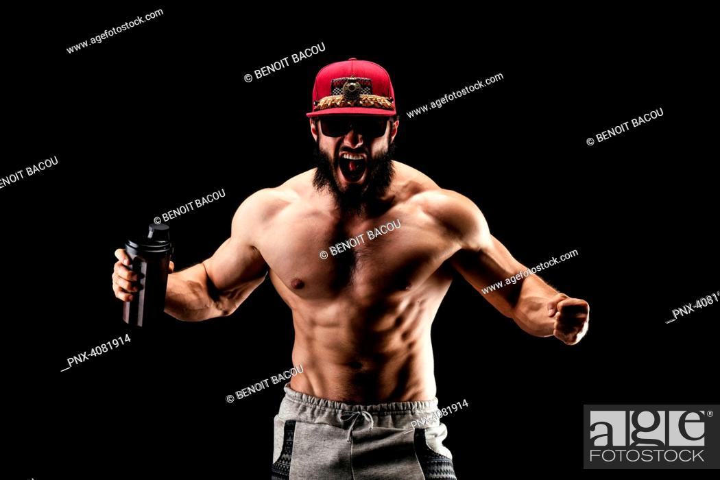 Stock Photo: Bodybuilder shouting, a protein shaker in his hand.