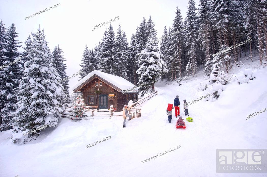 Stock Photo: Austria, Altenmarkt-Zauchensee, family with sledges at wooden house at Christmas time.