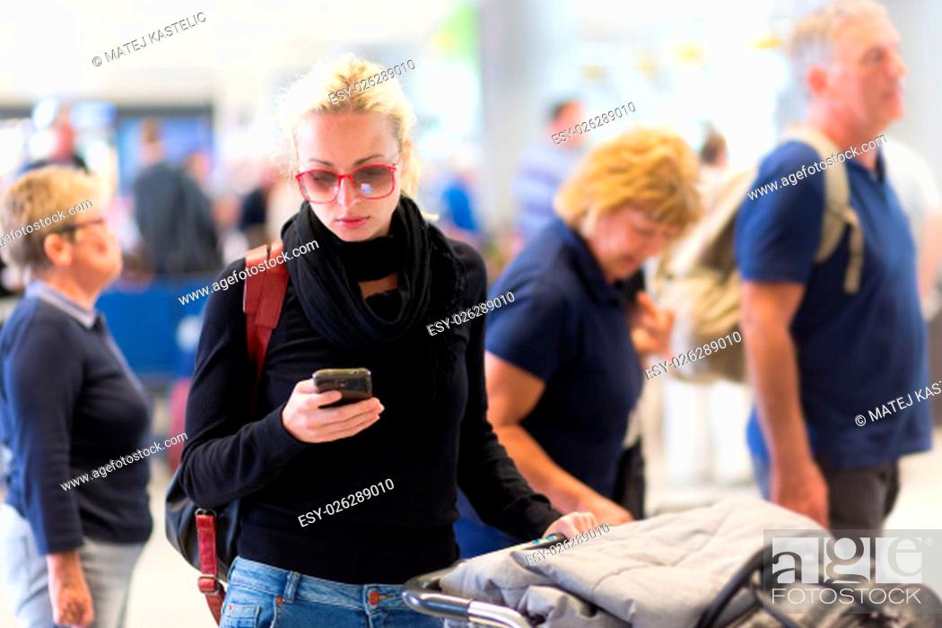 Stock Photo: Casual blond young woman using her cell phone while queuing for flight check-in and baggage drop. Wireless network hotspot enabling people to access internet.