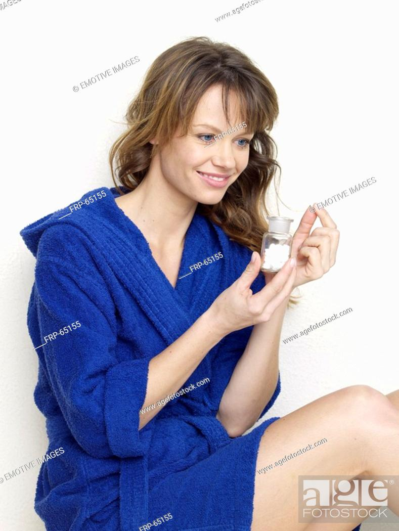 Stock Photo: Woman in blue bathrobe with pills.