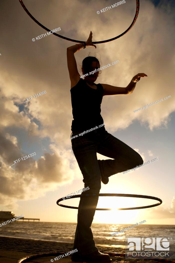 Stock Photo: A young woman student at Aberystwyth university using hoolah hoops at sunset, UK.