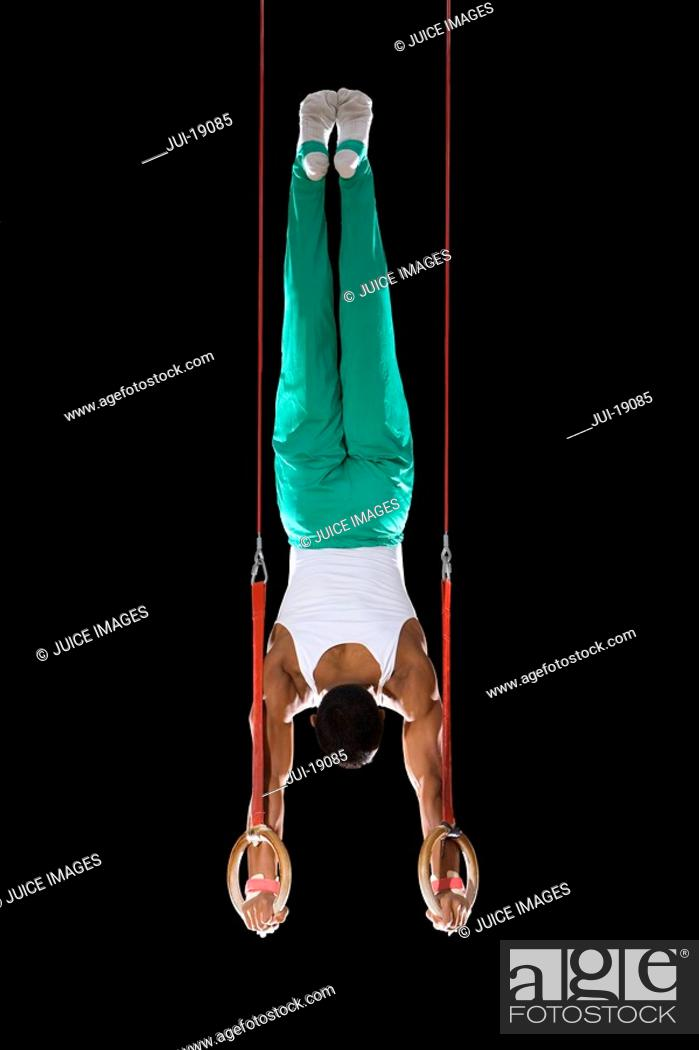Stock Photo: Male gymnast performing handstand on gymnastic rings, rear view.