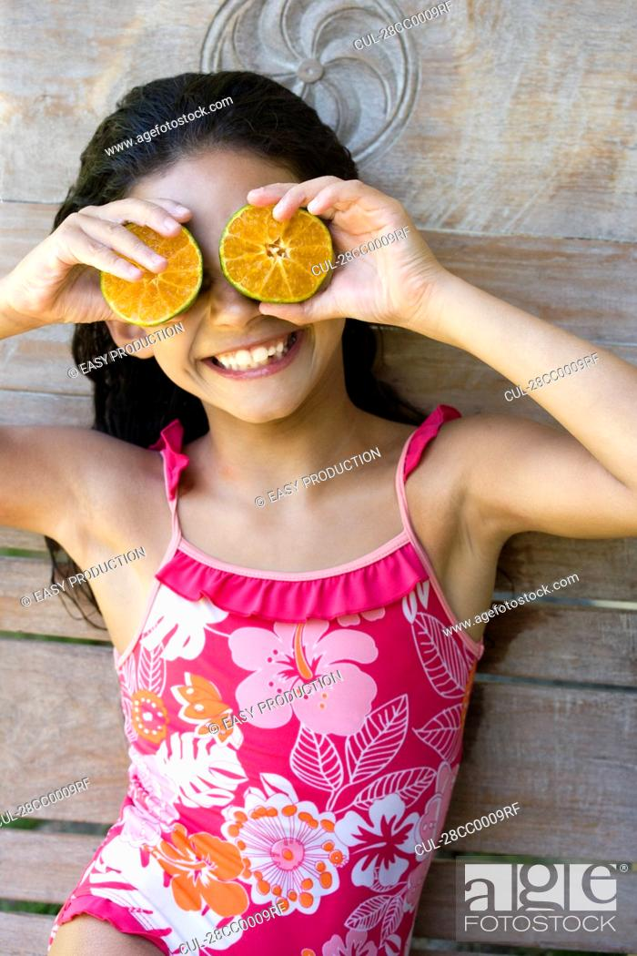 Stock Photo: Young girl using half fruits as eyes.