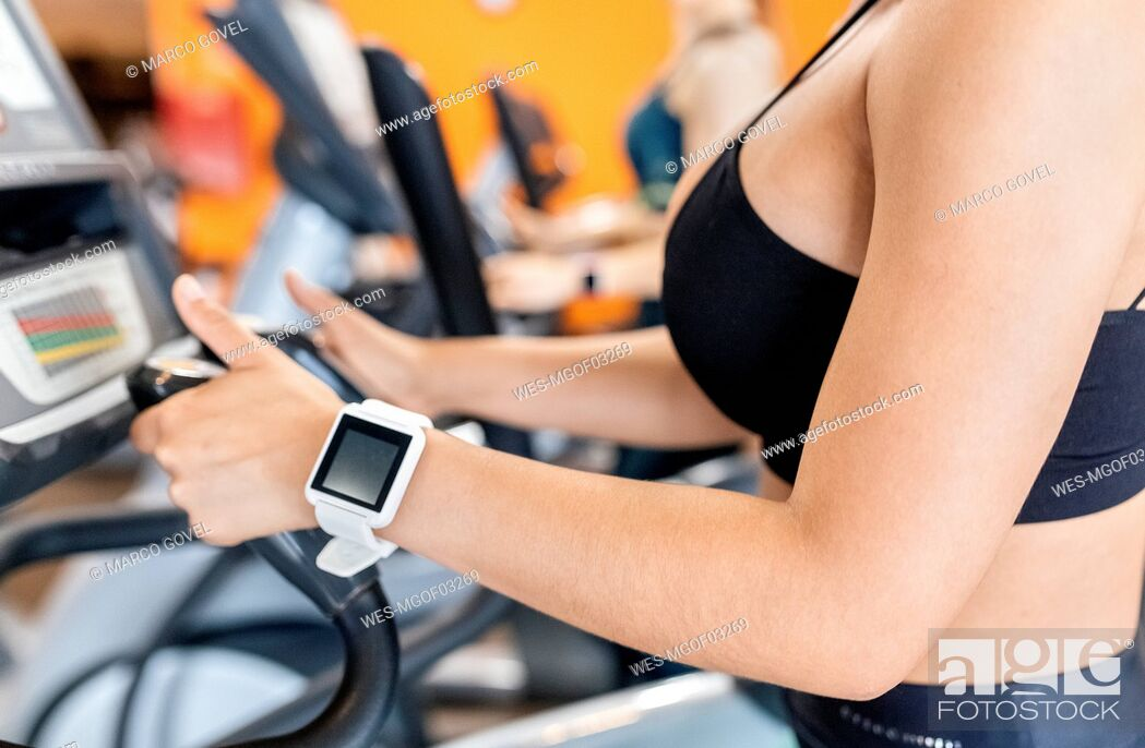Stock Photo: Woman in gym with smartwatch using an elliptical trainer.