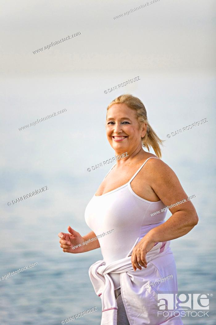 Stock Photo: Portrait of a senior adult woman running at the beach.